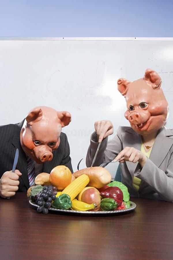 Zakenlui in varkensmaskers met plastic voedsel stock afbeeldingen