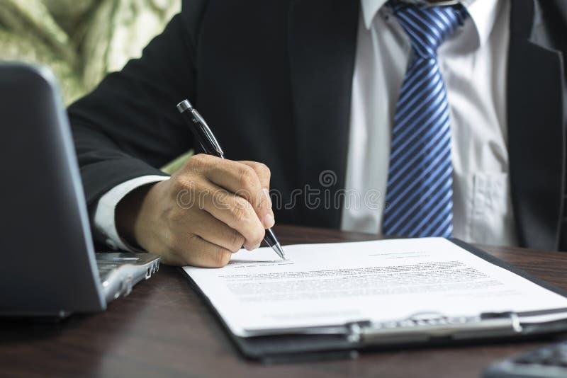 zakenman of advocaat die op contractdocument ondertekenen op lijst in offi stock fotografie