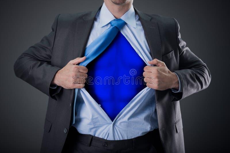 Zakenman als super held en tearing zijn overhemd stock fotografie