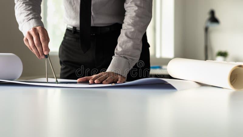 Zakenman of arhitect in grijs overhemd die heerser en paar van mede gebruiken royalty-vrije stock afbeeldingen