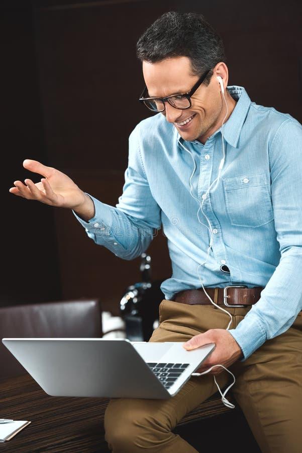 zakenman in bedrijfs toevallige kledingszitting op bureau en het letten van op iets op zijn laptop royalty-vrije stock foto's