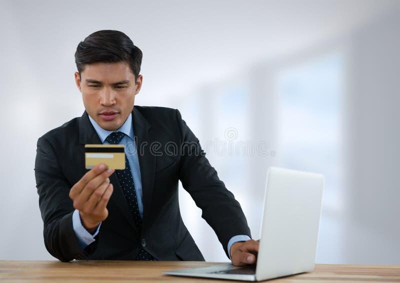 Zakenman bij bureau met laptop met heldere achtergrond met bankkaart royalty-vrije stock fotografie