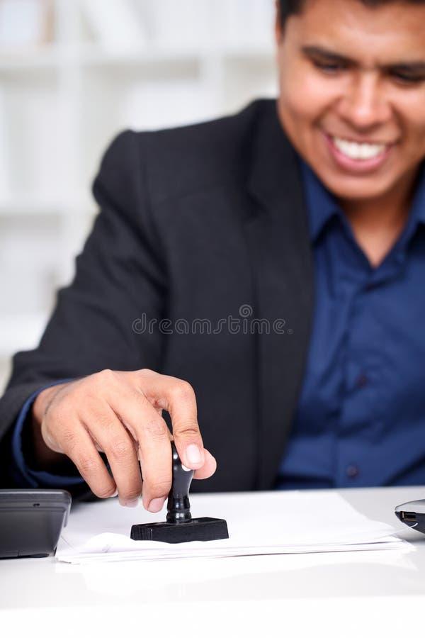 Zakenman bij zijn bureau het stempelen royalty-vrije stock afbeeldingen
