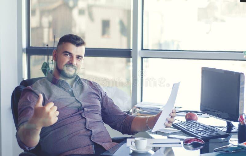 Zakenman in bureau, bij werkplaats met contract in handen Happ stock afbeeldingen