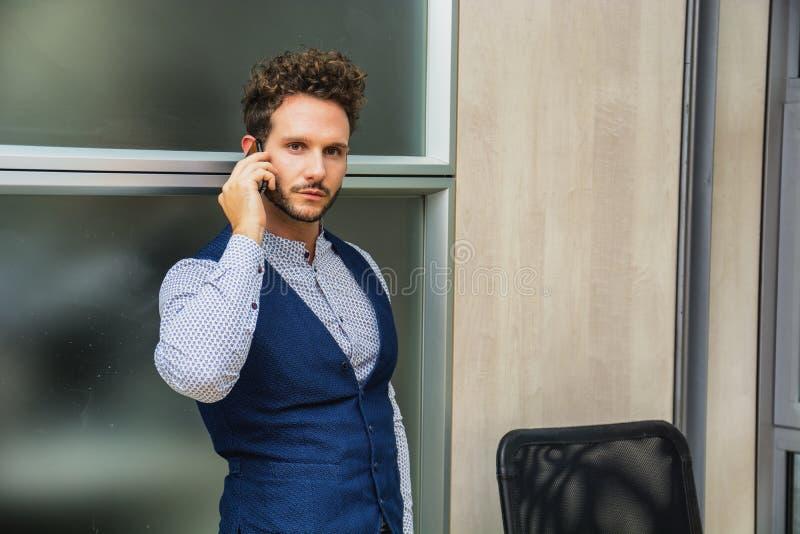 Zakenman in bureau die op celtelefoon spreken royalty-vrije stock foto