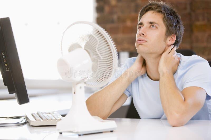 Zakenman in bureau met computer en ventilator stock foto's