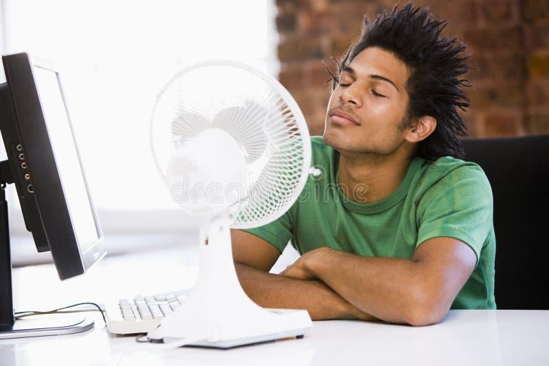Zakenman in bureau met computer en ventilator stock afbeeldingen