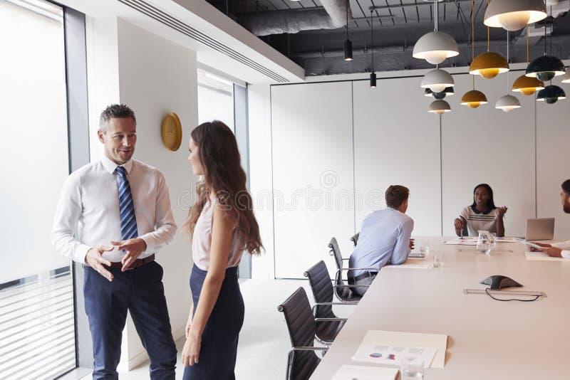 Zakenman And Businesswoman Standing in Moderne Bestuurskamer die Informele Bespreking met Collega's hebben die rond Lijst in Rug  royalty-vrije stock foto