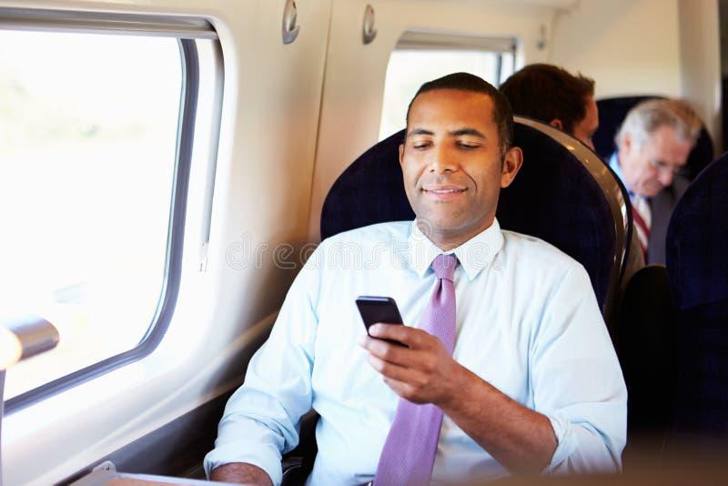 Zakenman Commuting To Work op Trein die Mobiele Telefoon met behulp van stock afbeeldingen