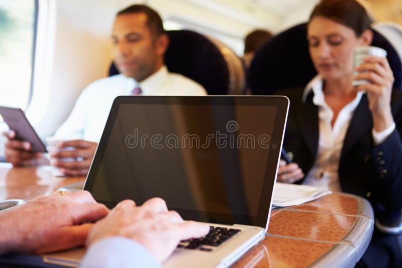 Zakenman Commuting To Work op Trein en het Gebruiken van Laptop stock afbeeldingen