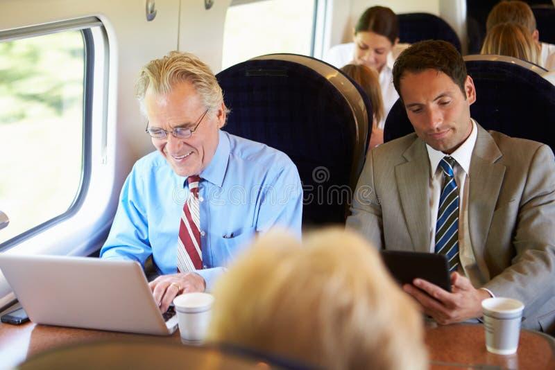 Zakenman Commuting To Work op Trein en het Gebruiken van Laptop stock foto's