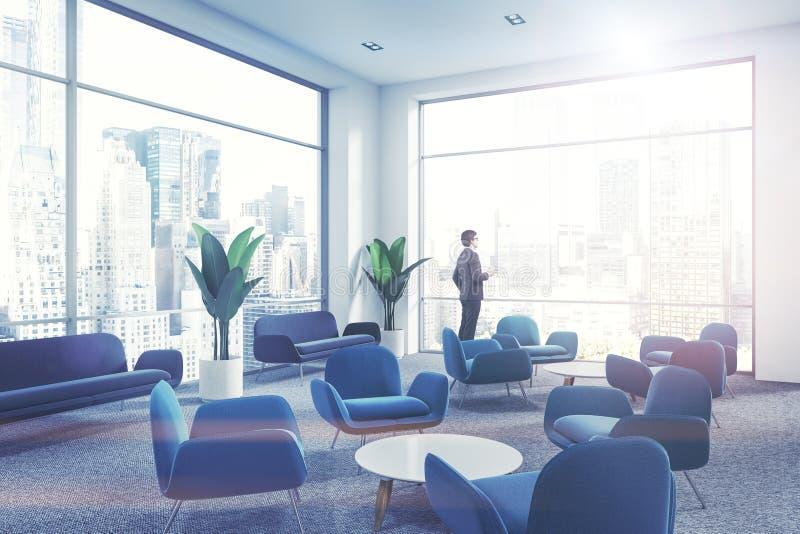 Zakenman in de blauwe wachtkamer van het leunstoelenbureau royalty-vrije stock foto