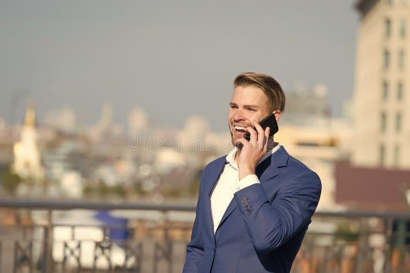Zakenman de gelukkige het glimlachen mededeling van gebruikssmartphone, horizonachtergrond De mens in kostuumzakenman neemt voord stock foto's