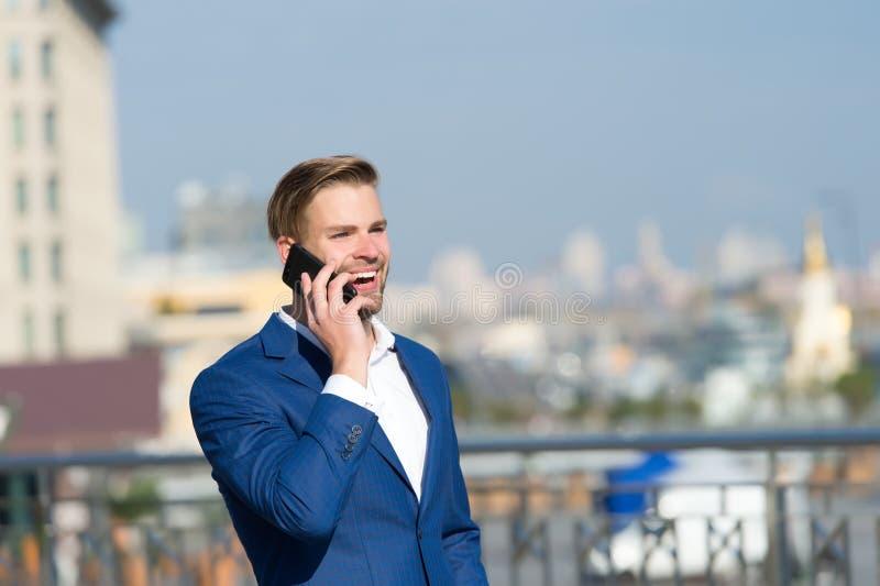 Zakenman de gelukkige het glimlachen mededeling van gebruikssmartphone, horizonachtergrond De mens in kostuumzakenman neemt voord royalty-vrije stock foto's