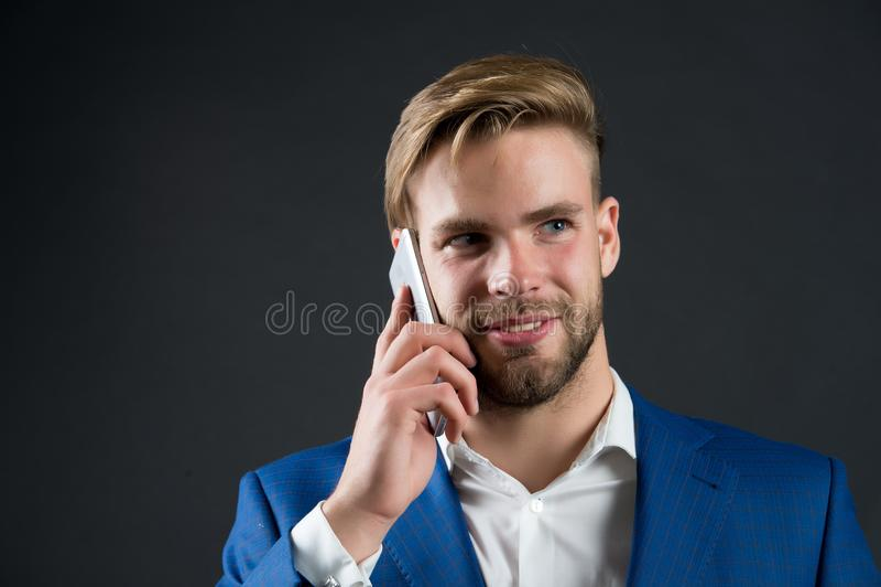 Zakenman de gelukkige het glimlachen mededeling van gebruikssmartphone, zwarte achtergrond Het bureau van de de celtelefoon van d royalty-vrije stock fotografie