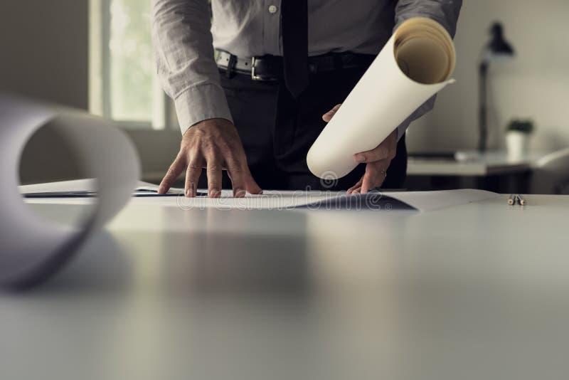 Zakenman die aan blauwdrukken in een bureau in een lage hoek vi werken royalty-vrije stock foto