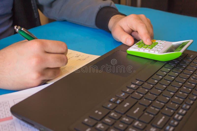 Zakenman die aan bureau met Calculator, een computer, een pen en documenten werken stock afbeelding
