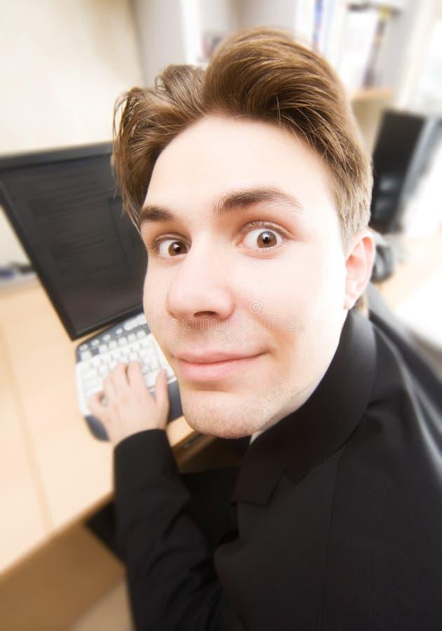 Zakenman die aan computer grappig portret werkt stock afbeeldingen