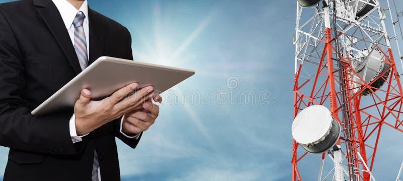 Zakenman die aan digitale tablet, met het satellietnetwerk van schoteltelecommunicatie op telecommunicatietoren werken op blauwe  stock afbeelding