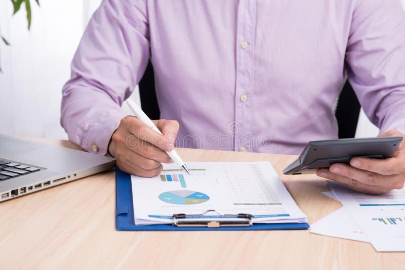 Zakenman die aan een bureau werken Freelance het werk thuis bureau Het schrijven nota over een boek Tijd het rennen Zachte nadruk royalty-vrije stock afbeeldingen