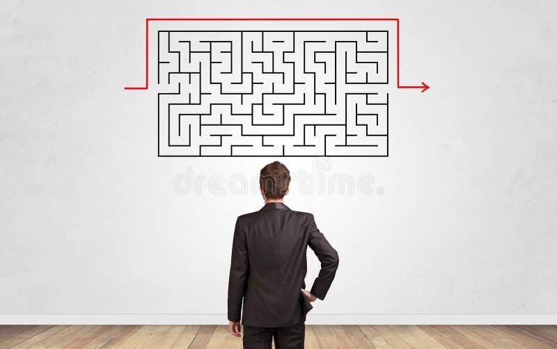 Zakenman die aan een labyrint op een muur kijken stock foto
