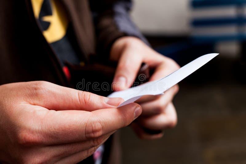Zakenman die aan een leeg document kijken Leeg Witboek in mensens handen Mannelijk holdingsblad van document De mens houdt een no royalty-vrije stock fotografie