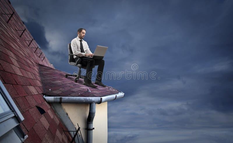 Zakenman die aan het dak werken royalty-vrije stock foto