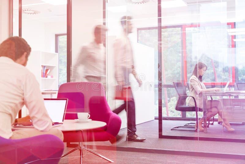 Zakenman die aan laptop in bestuurskamer met collega's op achtergrond op kantoor werken stock fotografie