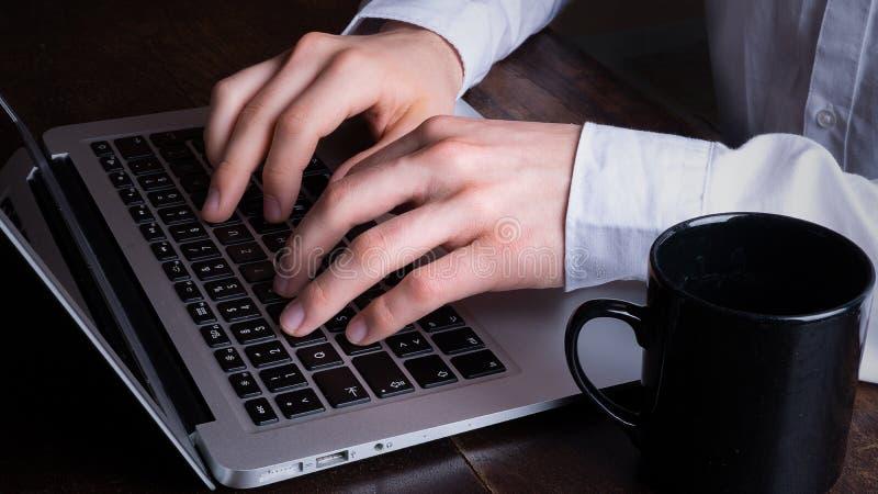 Zakenman die aan laptop in bureau werken stock foto