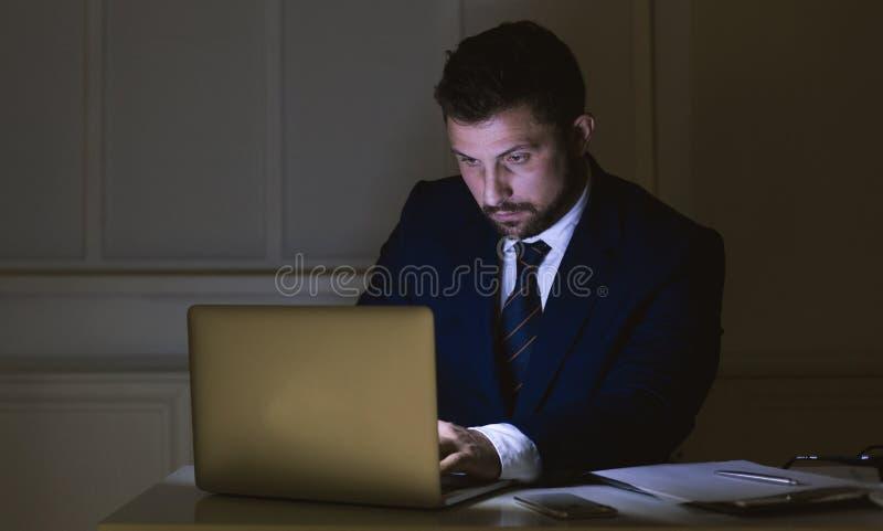 Zakenman die aan laptop in donker bureau werken stock foto's