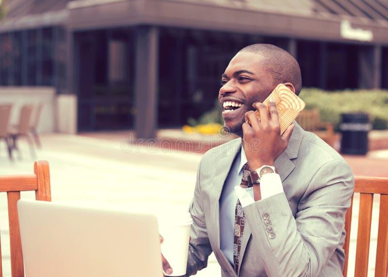 Zakenman die aan laptop werken die in openlucht op mobiele telefoon spreken stock foto