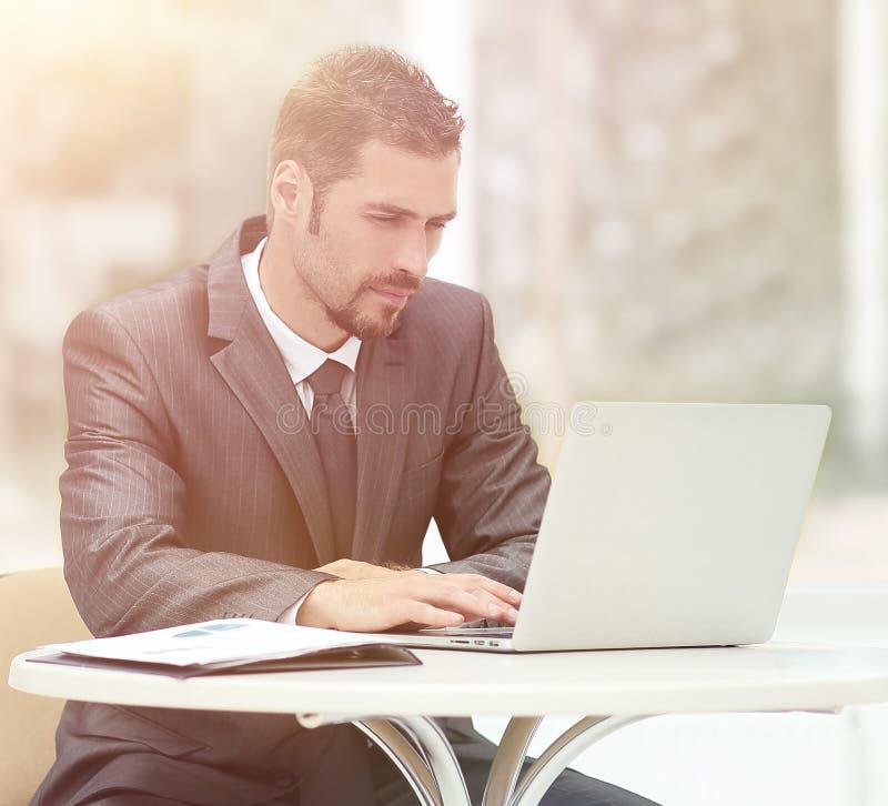 Zakenman die aan laptop werken terwijl het zitten bij een lijst in een coff royalty-vrije stock foto's