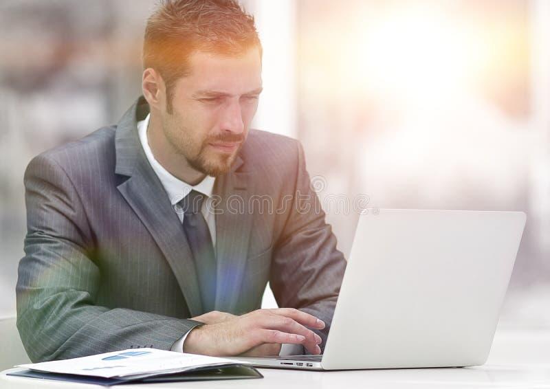 Zakenman die aan laptop werken terwijl het zitten bij een lijst in een koffie royalty-vrije stock afbeeldingen