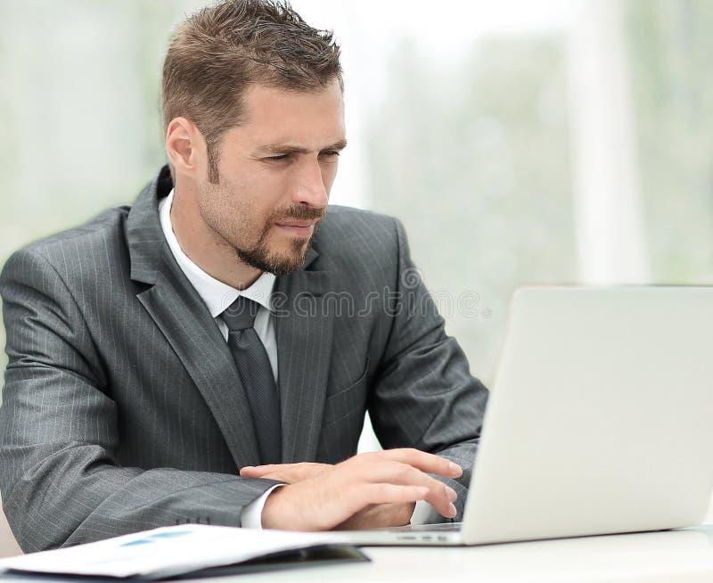 Zakenman die aan laptop werken terwijl het zitten bij een lijst in een koffie stock foto