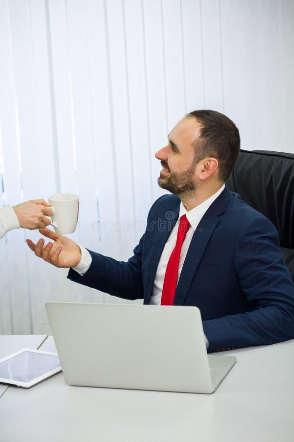 Zakenman die aan laptop werkt de secretaresse bracht hem koffie royalty-vrije stock fotografie