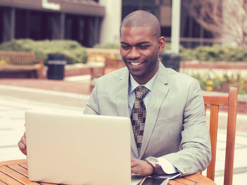 Zakenman die aan zijn laptop in openlucht collectief bureau werken stock afbeeldingen