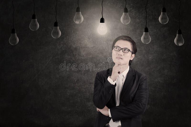 Zakenman die aangestoken bekijken lightbulb royalty-vrije stock afbeeldingen