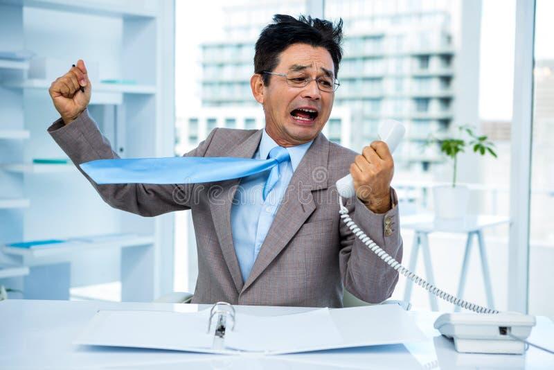 Zakenman die aangezien hij telefoon standhoudt schreeuwen royalty-vrije stock foto