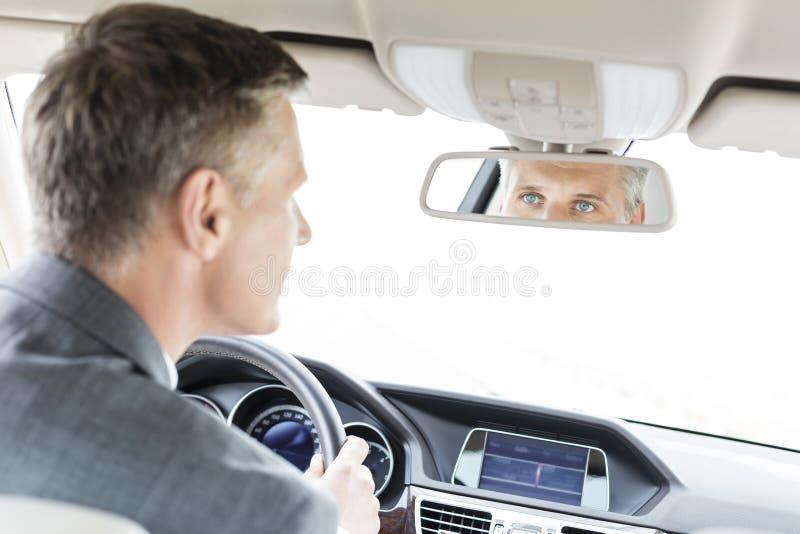 Zakenman die achteruitkijkspiegel van auto onderzoeken royalty-vrije stock afbeeldingen