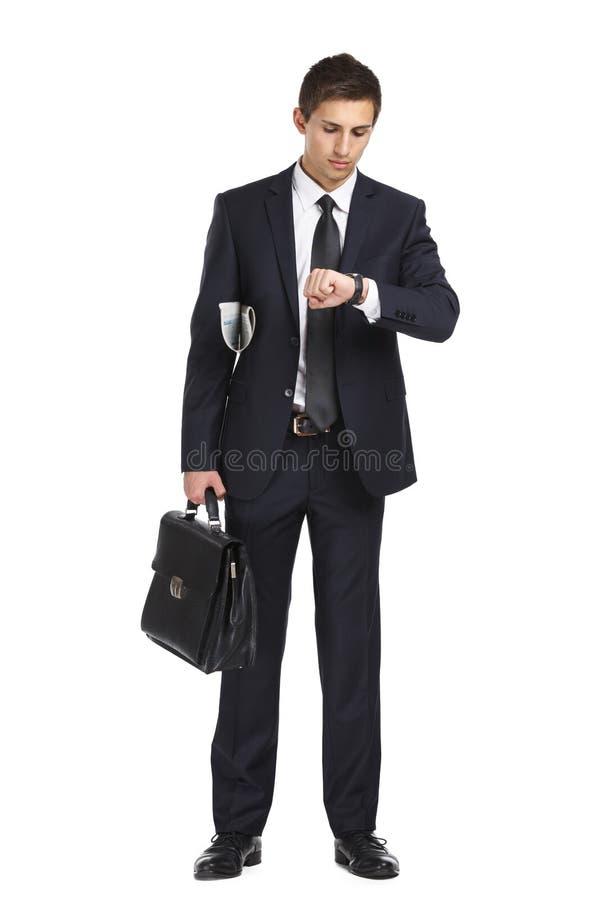 Zakenman die aktentas overhandigen en zijn horloge bekijken stock foto's