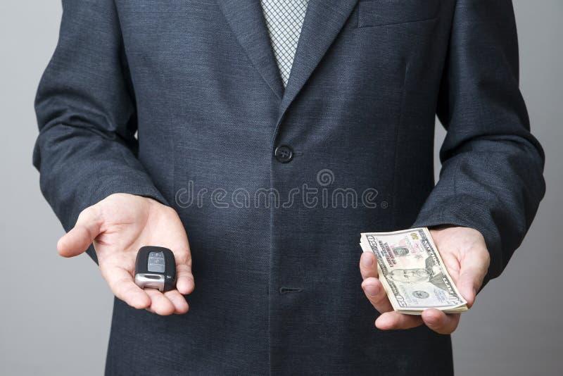 Zakenman die autosleutel en geld gebruiken royalty-vrije stock fotografie
