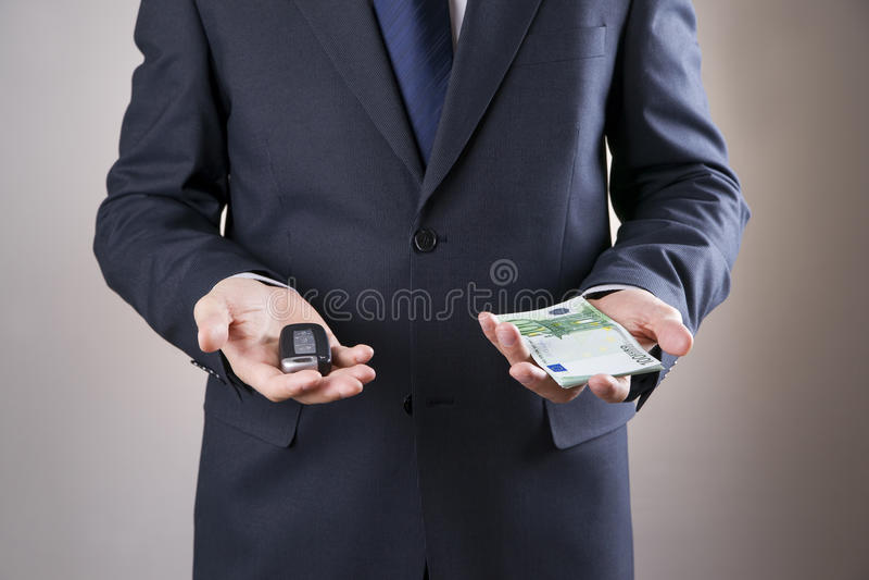 Zakenman die autosleutel en geld gebruiken royalty-vrije stock afbeeldingen