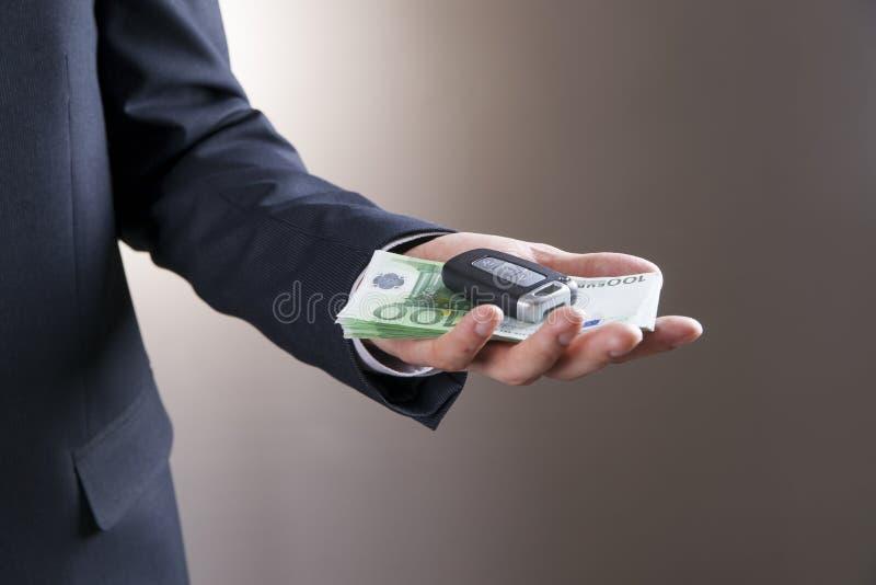 Zakenman die autosleutel en geld gebruiken stock afbeeldingen