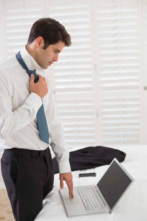 Zakenman die band dragen terwijl het gebruiken van laptop bij een hotelruimte royalty-vrije stock afbeelding