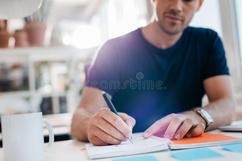 Zakenman die belangrijke nota's in agenda neerschrijven bij zijn bureau stock afbeeldingen