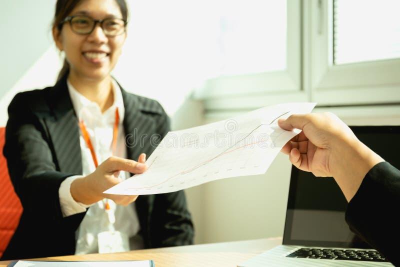 Zakenman die bij bureau met laptop werken die document grafiek overhandigen aan secretaresse royalty-vrije stock afbeeldingen