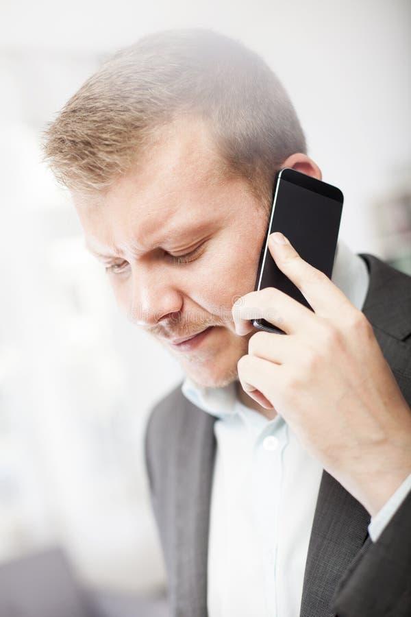 Zakenman die bij een vraag op zijn mobiel fronsen stock afbeeldingen
