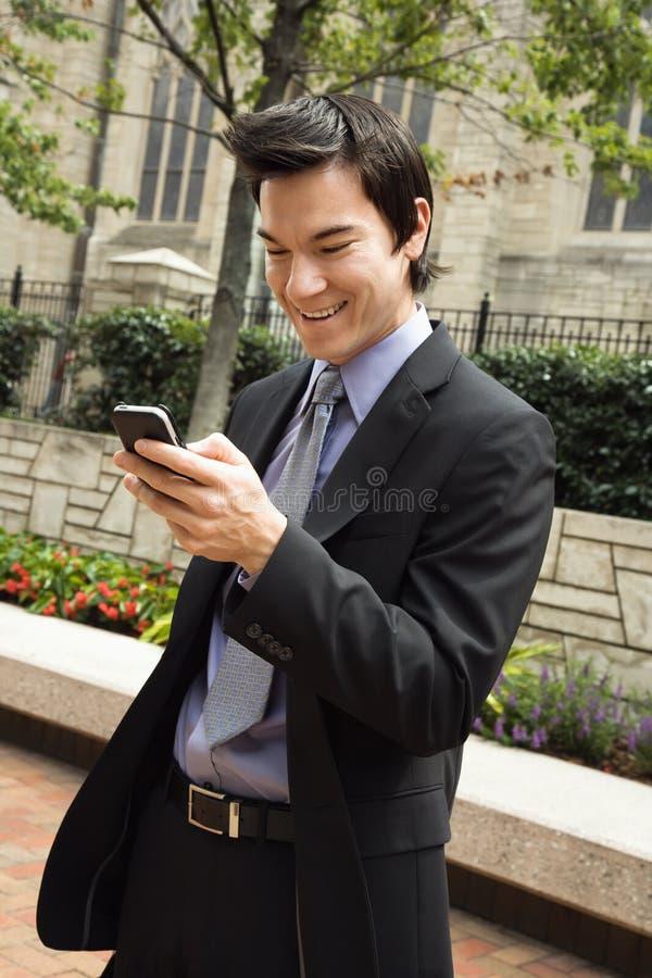Zakenman die bij het bericht van de celtelefoon glimlacht. stock afbeeldingen