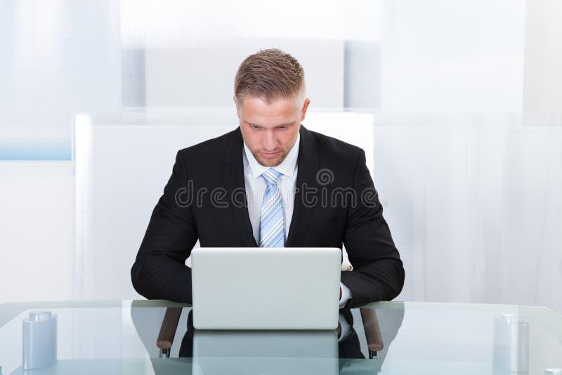 Zakenman die bij laptop werkt royalty-vrije stock afbeelding