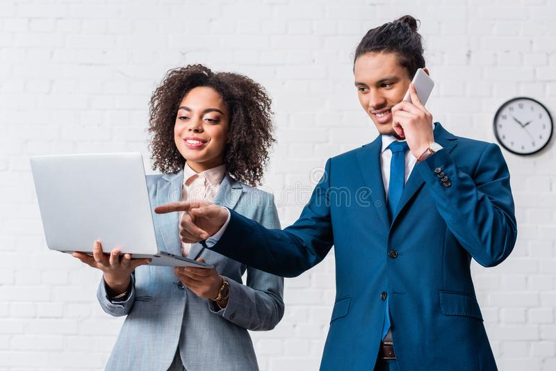 Zakenman die bij telefoon en onderneemster het kijken spreken royalty-vrije stock fotografie